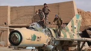 Combatientes de las Fuerzas Democráticas de Sirias posan este domingo subidos a un avión de combate desmantelado tras tomar el control del aeropuerto militar deTabqa, que estaba en manos del Estado Islámico.