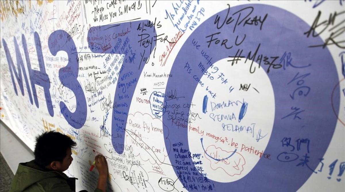Un hombre escribiendo mensajes en honor a las víctimas del vuelo MH370 de Malaysia Airlines en el aeropuerto internacional de Kuala Lumpur, enMalasia.