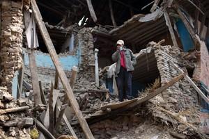 Un hombre en pie entre las runas de un edificio destruido por el terremoto de Nepal