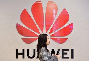 Una personapasaenfrente del logotipo de Huawei.