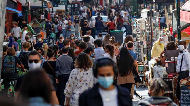 Más de un millón de fallecidos por coronavirus en todo el mundo. En la foto, paseantes con mascarilla por las calles de París.