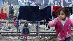 Niños refugiados juegan entre ropas colgadas para secar entre alambradas en un campo de refugiados de Idomeni (Grecia), junto a la frontera con Macedonia.