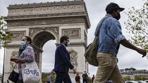 Parisinos con mascarilla caminan por los Campos Elíseos, con el Arco de Triunfo detrás, este viernes.