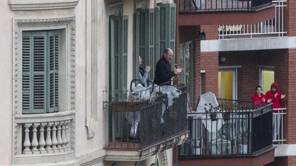 Personas aplauden desde los balcones del Eixample, el pasado 30 de marzo.