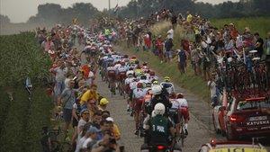 Los espectadores arropan a los ciclistas en el tramo de adoquines de la primera etapa.