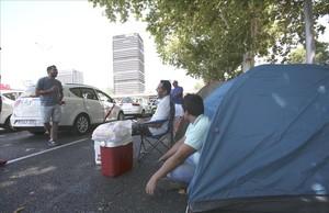 Numerosos taxistas han pasado la noche del lunes acampados en el Paseo de la Castellana de Madrid y utilizan ahora sus tiendas para refugiarse del calor.