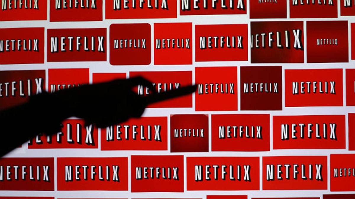 Sombra de un hombre sujetando un mando a distancia sobre el fondo del logo de Netflix.