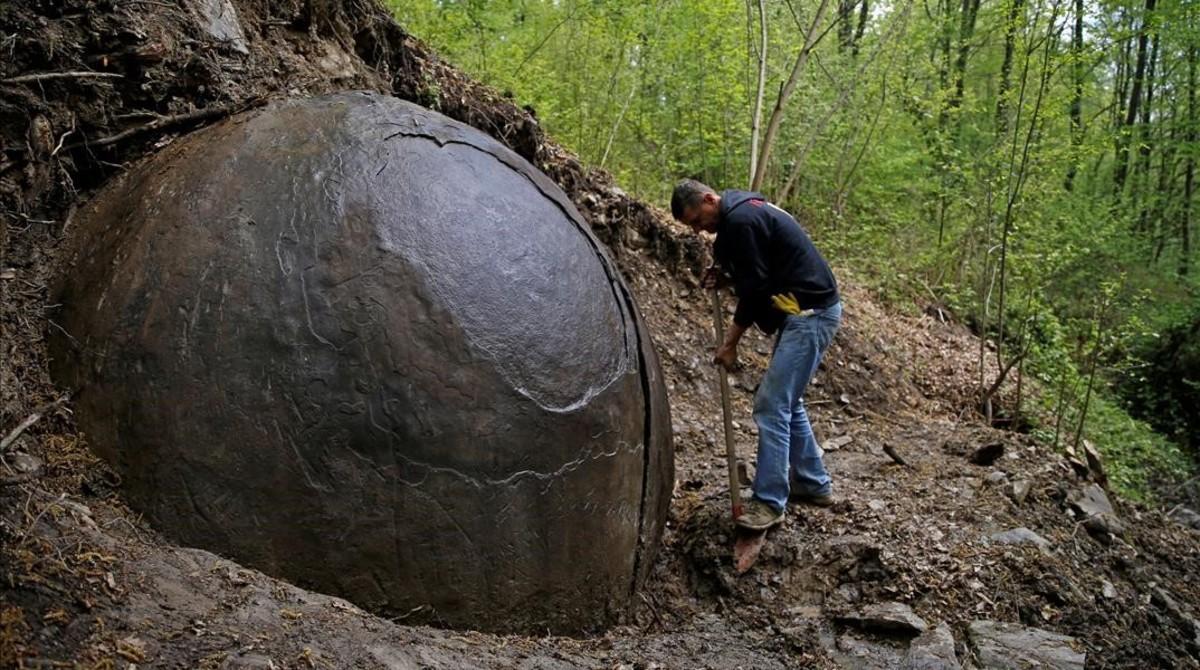 Suad Keserovic limpia la esfera de piedra en Podubravije, cerca de Zavidovici (Bosnia), el 11 de abril.