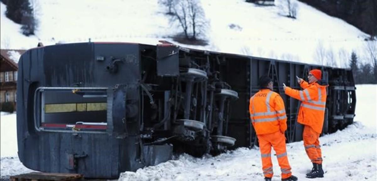 Dos trabajadores inspeccionan el vagón de un tren de pasajeros que ha descarrilado en Suiza debido al paso de Eleanor.
