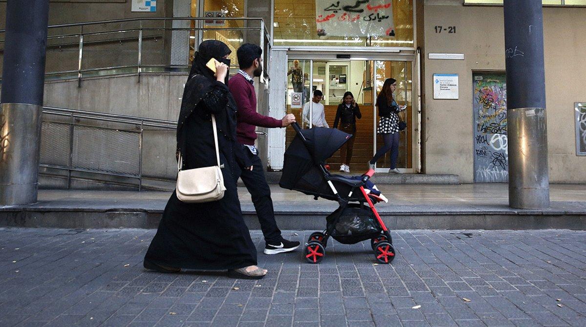Una joven familia inmigrante pasea por el centro de Barcelona.