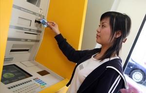 Una joven saca dinero de un cajero.