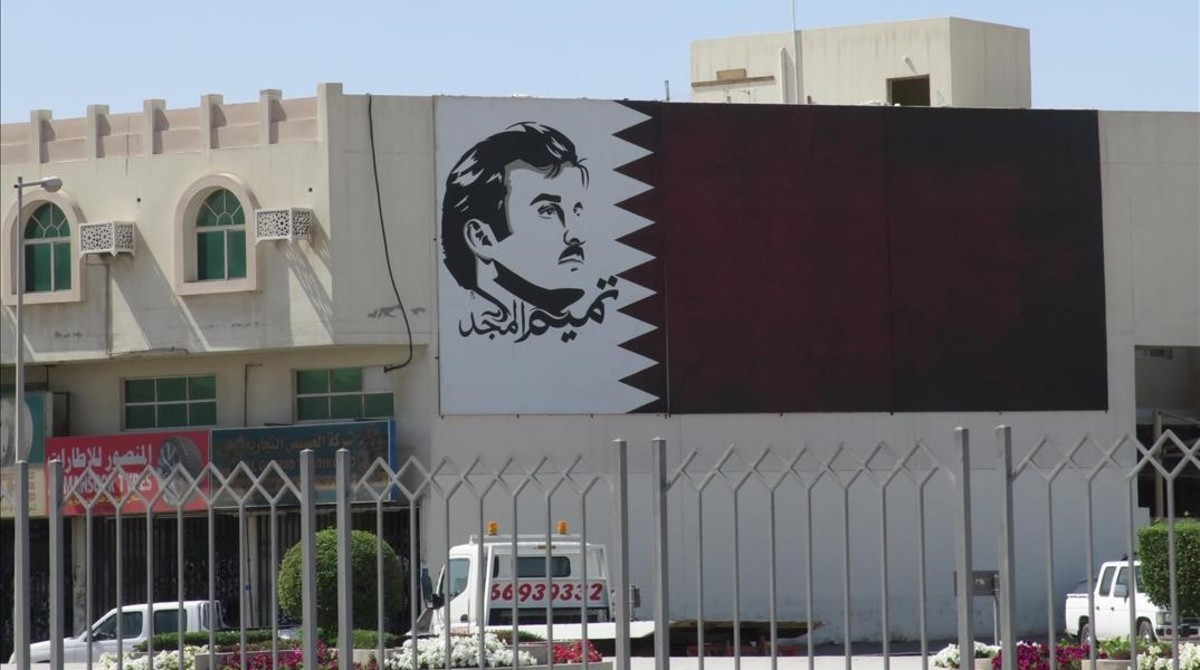 Una de las múltiples fachadas de edificios y calles de Doha decoradas con la bandera catarí y el retrato de su joven emir.
