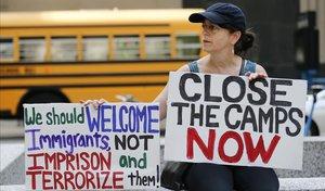 Una manifestante sostiene dos pancartas dando la bienvenida a los inmigrantes irregulares y reclamando el cierre de los centros de detención.