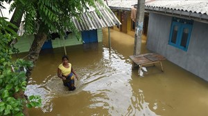 Una mujer se abre paso entre el agua en el suburbio de Kelaya, en Colombo.