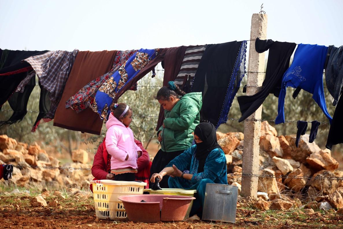 Una mujer y sus hijas lavan la ropa en Jarufiya.