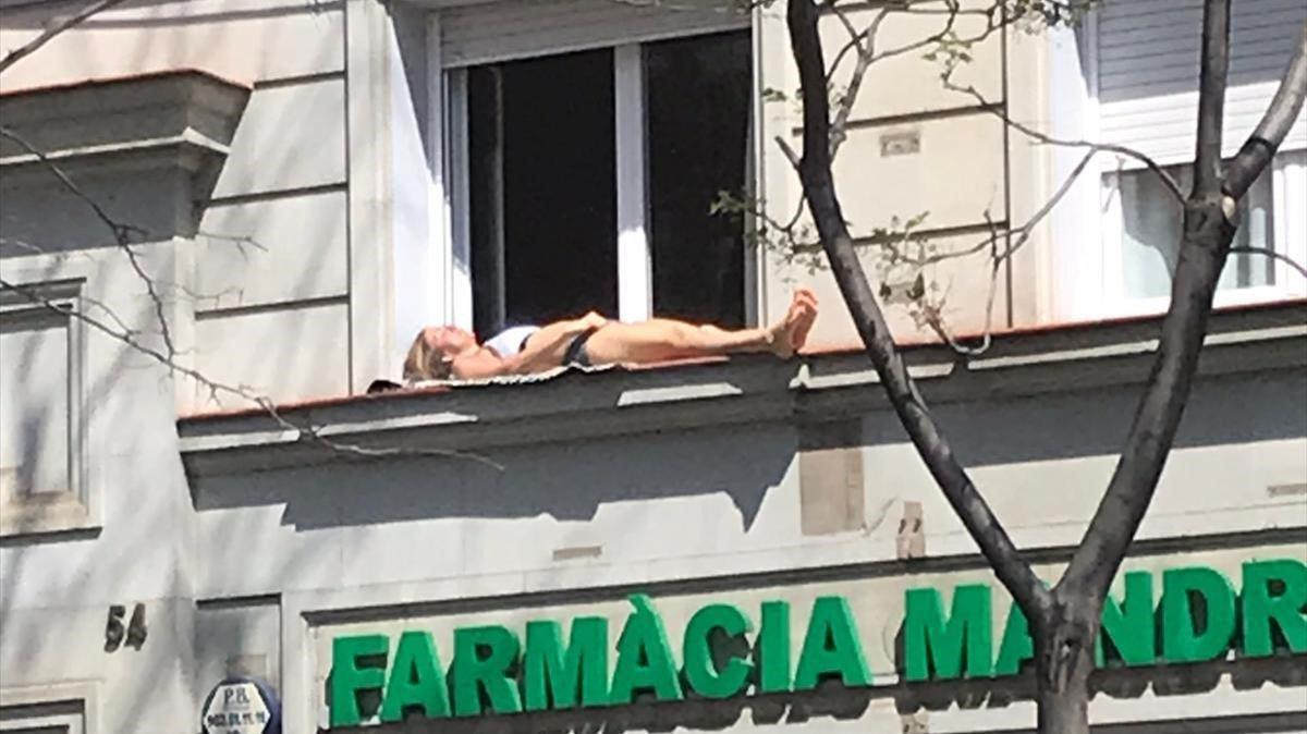 Una mujer toma el sol en la cornisa de una ventana en la calle de Mandri.