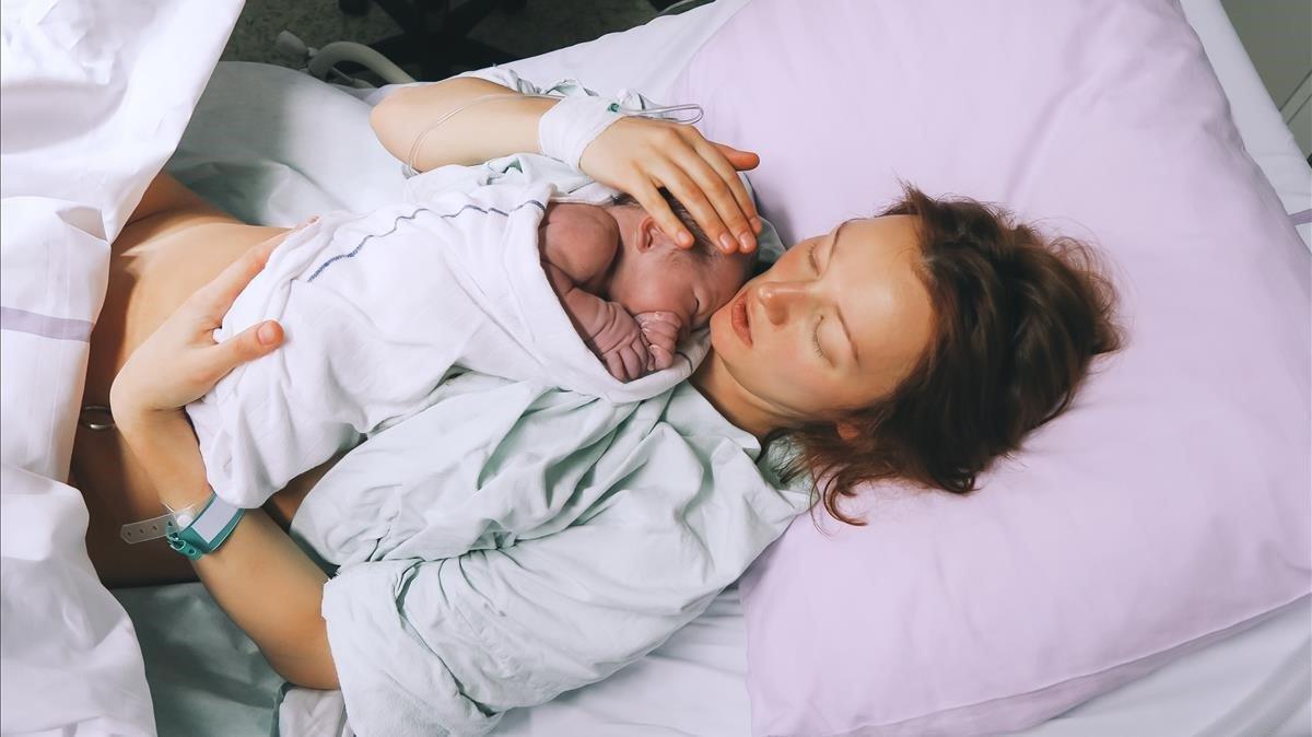 Una mujer con su bebé en brazos.