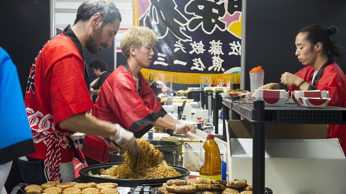 Unos cocineros preparan fideos en la zona de restauración japonesa.