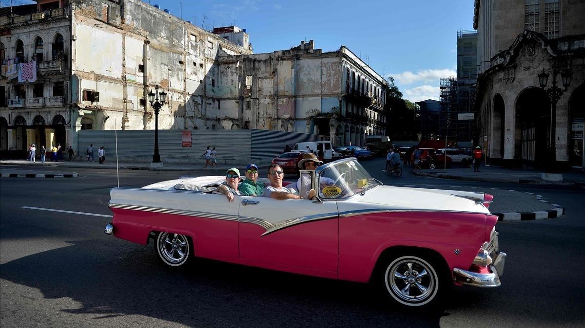 Unos turistas dan un paseo en un vehículo clásico utilizado como taxi en La Habana, el pasado 6 de mayo.