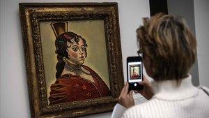 Una visitante fotografíaun cuadro de Joan Miró en la exposición de París del Grand Palais.