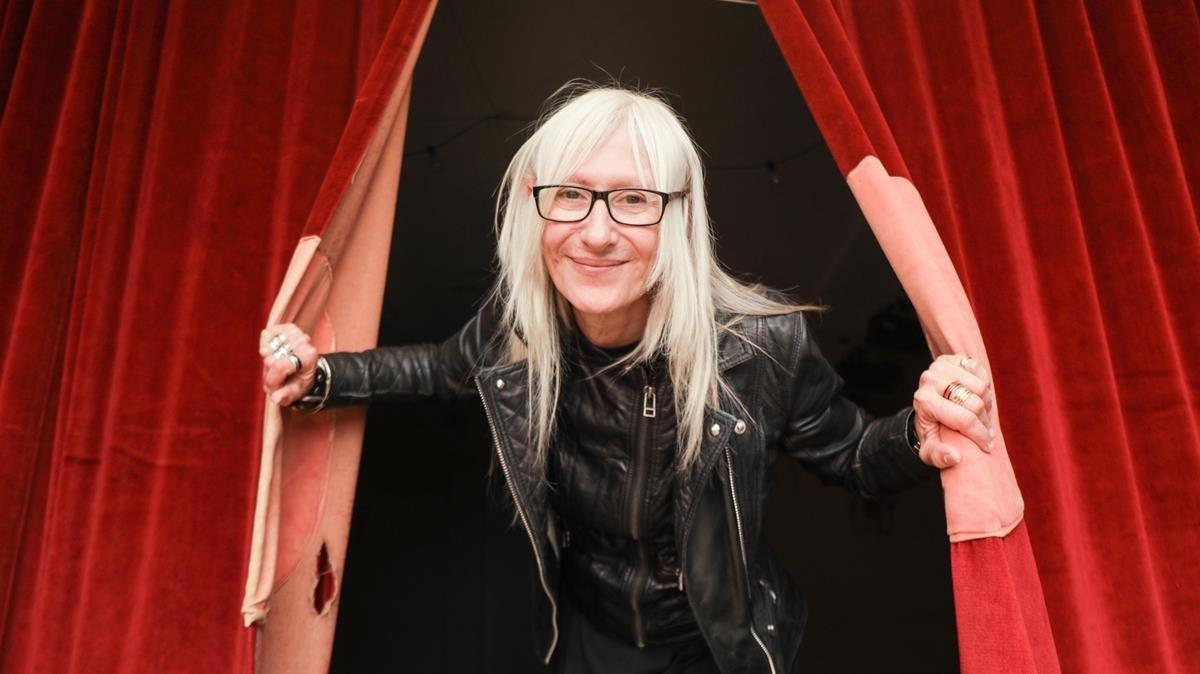 Tina Gil asoma entre los cortinajes del teatro del Foment Martinenc, sede laAssociació de Músics del Carrer i del Metro de Barcelona, a la que pertenece.
