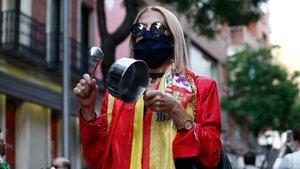 Una mujer protegida con mascarilla golpea una cacerola durante la manifestacion celebrada en la puerta de la sede del PSOE de la calle Ferraz de Madridcontra la gestion del Gobierno de Espana en la crisis del coronavirus.
