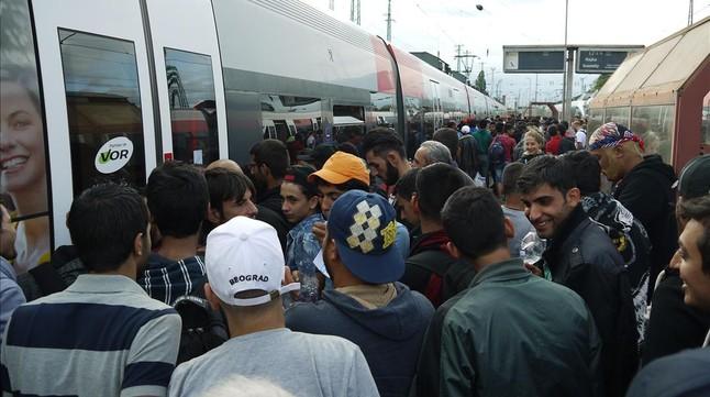 Los refugiados se amontonan a la espera de poder subir al tren con destino a Austria.