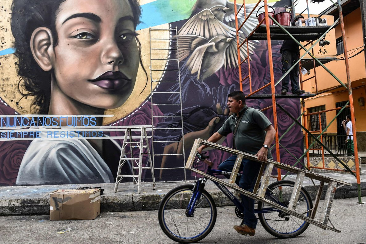 A man rides  his bicycle past an artist working on a mural, during the First International Mural Festival for Peace in San Carlos. According to the event organizers the Mural Festival is aimed at changing the negative perception of the town, known mostly for its violent past. (Photo by JOAQUIN SARMIENTO / AFP)