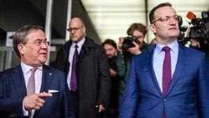Armin Laschet (izquierda) conversa con Jens Spahn tras la conferencia de prensa conjunta que han celebrado en Berlín.