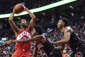 Toronto Raptors forward Kawhi Leonard  2  goes to the net against Chicago Bulls forward Justin Holiday  7  and forward Wendell Carter Jr   34  during second-half NBA basketball game action in Toronto  Ontario.  Frank Gunn The Canadian Press via AP