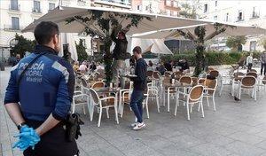 Un policía municipal de Madrid observa el cierre y recogida de una terraza.