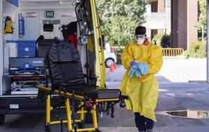 Técnicos sanitarios desinfectan una ambulacia en el Hospital de Igualada.