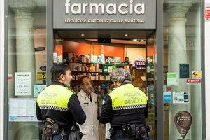 Dos agentes de la polícia local de Sevilla hablan con un farmacéutico en la puerta de su local.