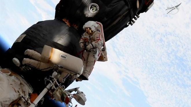 Dos astronautas reparan el casco de la Soyuz durante un paseo espacial.
