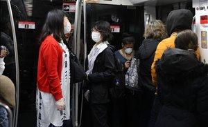 Dos chicas con mascarilla por temor al coronavirus en el metro de Barcelona.
