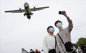 Dos jóvenes con mascarillas para protegerse frente al coronavirus se retratan en el aeropuerto de Taipei (Taiwán).