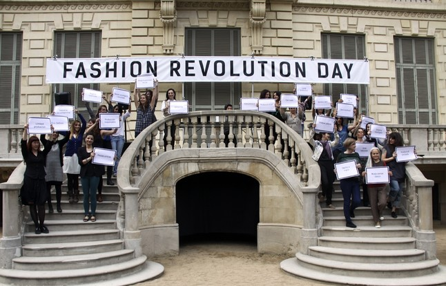 Los diseñadores y vendedores muestran sus pancartas reivindicativas al finalizar la pasarela en el Palau Robert.
