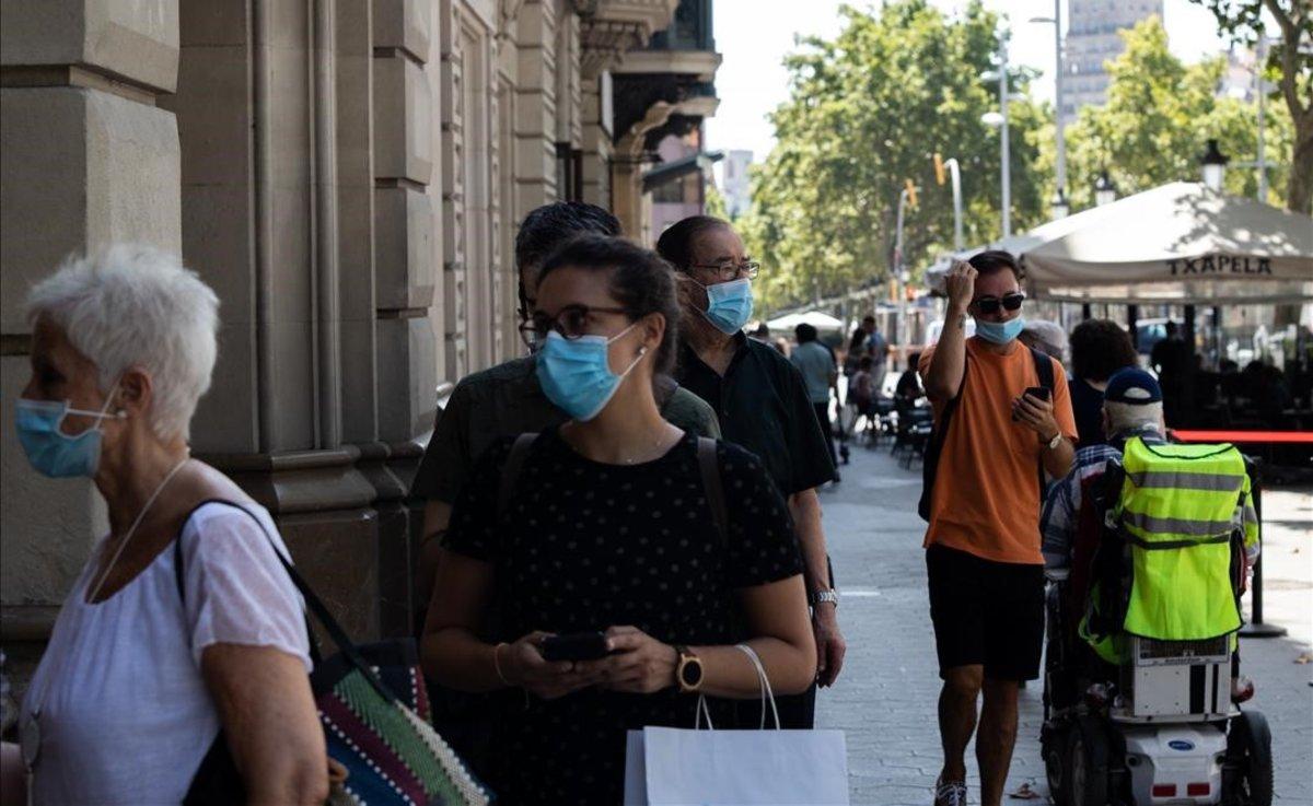 Gente con mascarilla en el paseo de Gràcia de Barcelona.
