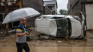 Un hombre anda frente a los destrozos causados por las lluvias en Japón.