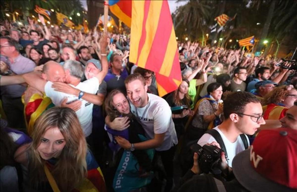 Personas concentradas en el paseo de Lluís Companys de Barcelona se abrazan durante la comparecencia del president.