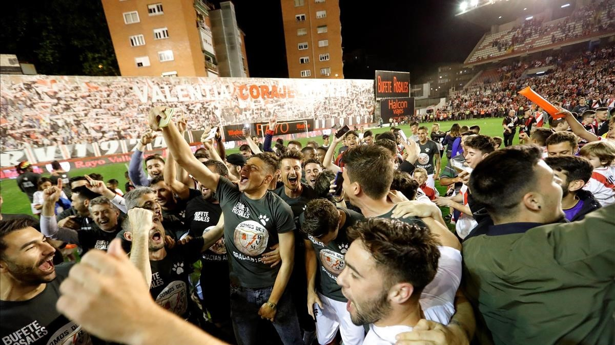 Jugadores y aficionados del Rayo celebran el ascenso a Primera en Vallecas el pasado mayo