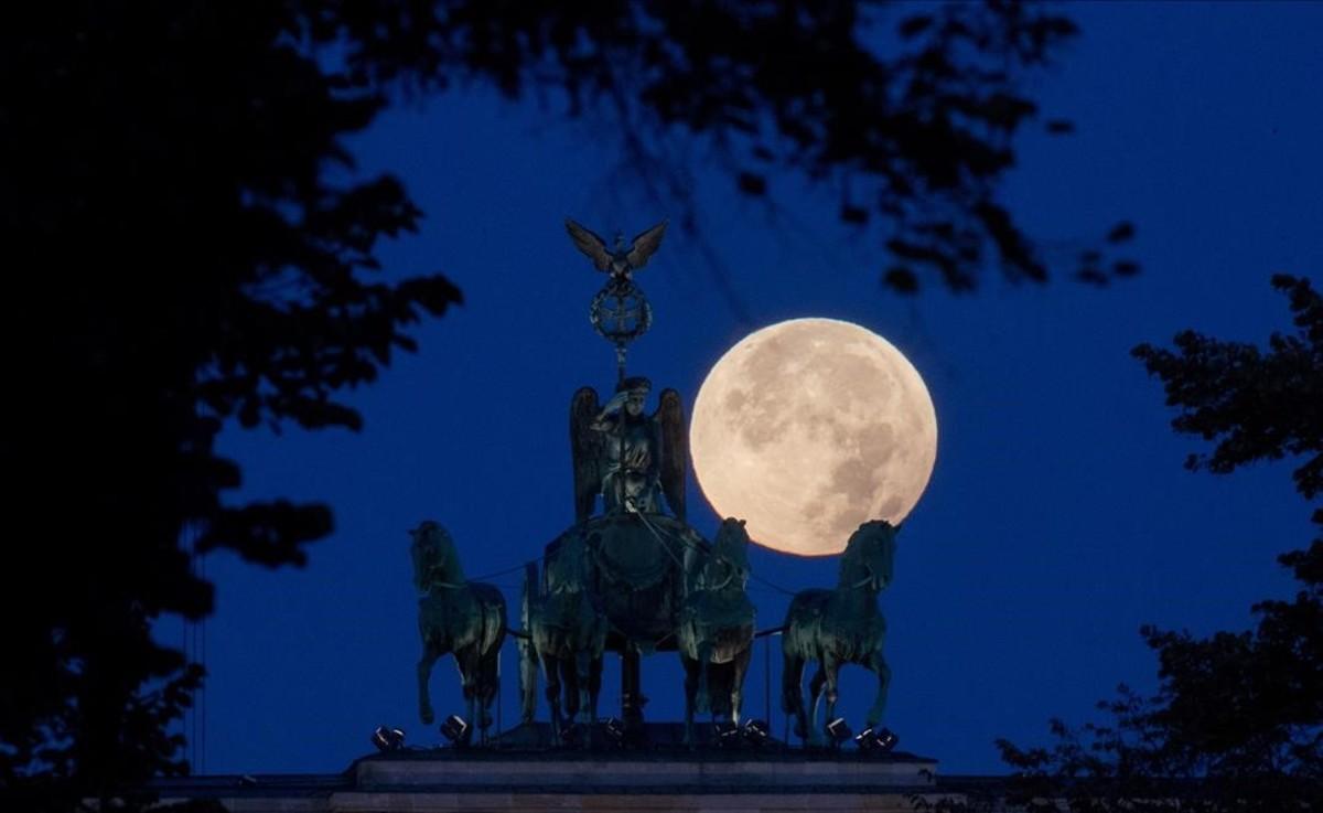 Detalle de la puerta deBrandenburgo, en Berlin, con la luna en su plenitud.