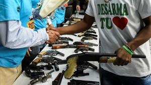 Un miembro de una banda entrega su arma en una ceremonia en Cali, el pasado julio.
