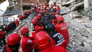 Miembros de los equipos de salvamento recuperan un cadáver de debajo de un edificio afectado por el terremoto, este sábado en Elazig.