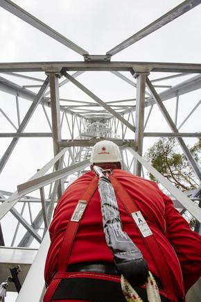Operario revisa torre de antenas de Vodafone.