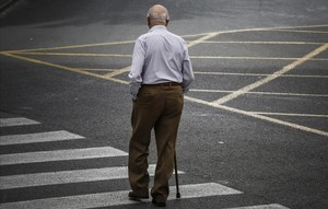 Un pensionista atraviesa una calle.