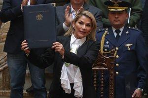 AME9218. LA PAZ (BOLIVIA), 24/11/2019.- La presidenta interina de Bolivia, Jeanine Áñez, sostiene un documento durante la promulgación de una ley de urgencia este domingo en La Paz (Bolivia). La ley de urgencia para convocar lo antes posible nuevos comicios en Bolivia fue promulgada este domingo por la presidenta interina del país, Jeanine Áñez, con el compromiso de que serán unas elecciones limpias, justas y transparentes. EFE/Rodrigo Sura