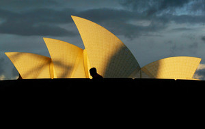 A tourist walks past the Sydney Opera House as a storm approaches overhead at sunset May 30, 2002. Australias top tourism attraction will receive a $A69 million (US$31 million) make-over during the next six years which will follow designs by the original Danish architect Joern Utzon. The improvements will include the construction of grand columns on the ground level, the orchestra pit will be extended and the seating refurbished, which will mean it will be closed for a year from late 2004. REUTERS/David Gray