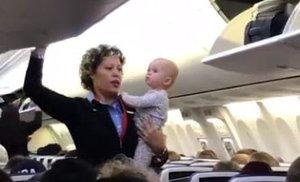 Una azafata carga con un bebé mientras prepara el avión para tranquilizarlo antes del vuelo
