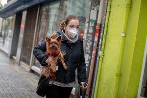Una mujer camina por la calle con su perro.
